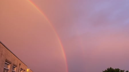 Double rainbow in evening sky above house. HD Footage.