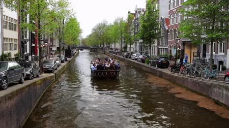 The most famous canals and embankments of Amsterdam with moving passenger boat. General view of the cityscape and Netherlands architecture. HD Footage. Стоковые видеозаписи