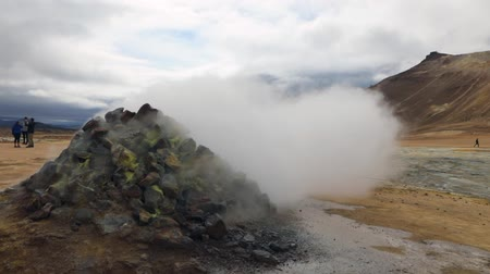 géiser : Icelandic geyser vapors and picturesque nature with moving tourist. HD Footage.
