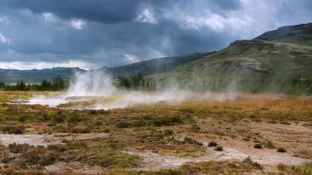 geotermální : Icelandic geyser vapors and picturesque nature with moving tourist. HD Footage.