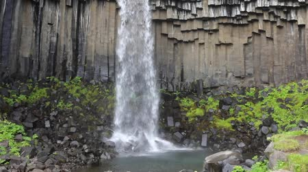 Picturesque landscape of a mountain waterfall and traditional nature of Iceland. Slow Motion Footage.