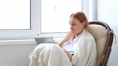 partially : woman relaxing in a white wicker chair in her living room working on a laptop