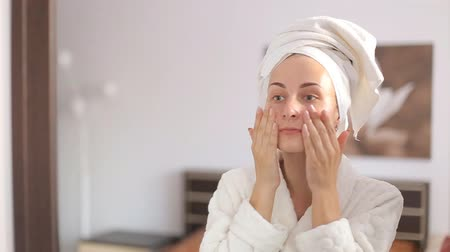 pleťová voda : Beautiful woman applying skincare lotion to face caring for skin