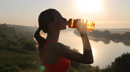 woda mineralna : Sporty Woman Drinking Water at Sunset after Running. Slow Motion. Wideo
