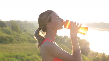 calor : Sporty Woman Drinking Water at Sunset after Running. Slow Motion. Vídeos