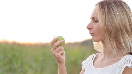 hassaslık : Caucasian woman with a toothpain sitting on a park bench and eating green apple Stok Video