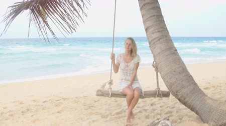 opalenizna : Beautiful woman smiling on a swing on the beach