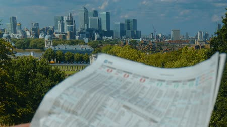 бычий : Investor reading a newspaper with Londons financial district in the backdrop