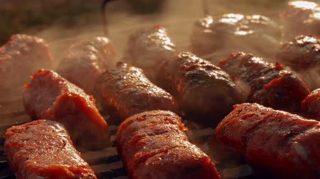 mici : An ultra close-up shot of a barbecue (BBQ) grill showing pork and beef meat rolls.