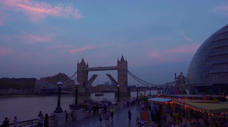 zajímavosti : An ultra slow motion view of the Southbank of the River Thames during twilight featuring the famous Tower Bridge with open lifts