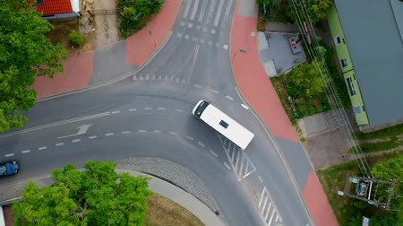 Two cars passing by across curved intersection in city, aerial view Stok Video