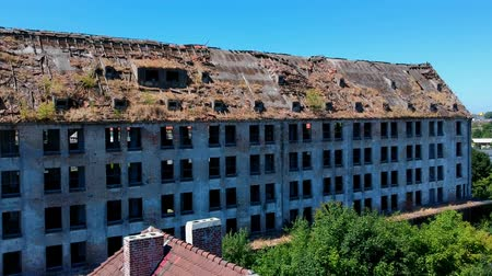 Flying slowly towards old ruined and destroyed industrial building, aerial view Stok Video