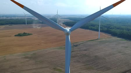 Aerial view on spinning blades of wind turbine tower on wheat field