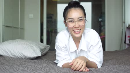 çok güzel : close up portrait young Asian woman laughing shows sign symbol OK on bed. attractive millennial girl looking at the camera smiling