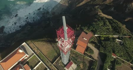 z lotu ptaka : Red white lighthouse, westernmost mainland Europe, Cape Roca, Portugal. Aerial shot of famouse lighthouse. Mountain landscape, Atlantic ocean birds eye view. Wild nature. Wideo