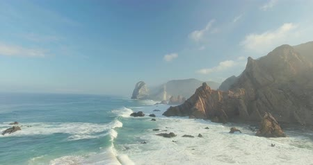 z lotu ptaka : Beautiful aerial or drone shot along the coast of Portugal on a sunny day. Epic cliffs and ocean waves birds eye view during sunrise. Untouched, powerful nature. Cabo da Roca, Portugal Europe.