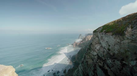 portugese : Slow motion shot of Cabo da Roca (Cape Roca), Portugal. The most westerly point of mainland Europe on a sunny summer or spring day. View of beautiful cliffs and rocks, Atlantic ocean waves.