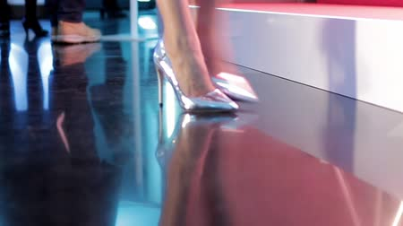 calçados : Close-up shot of a pair of beautiful female legs wearing high silver heels walking away from to the camera. Zooms in to follow. Stock Footage