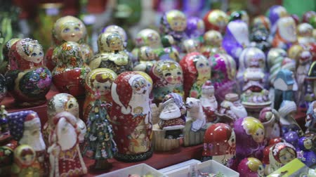 aninhada : Many colorful Russian wooden souvenirs (matrioshka, nesting dolls) on the counter at a christmas fair. Stock Footage