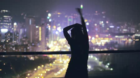 jovem : Young beautiful woman dancing on terrace during night. Young excited woman dancing on the rooftop, enjoying breathtaking view over the city at night. City lights, Party time.