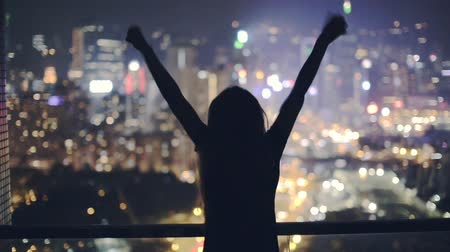 vencedor : Silhouette of a young happy girl feeling awesome on the rooftop with great view over city. Success and happiness concept. Hong Kong, China. Vídeos