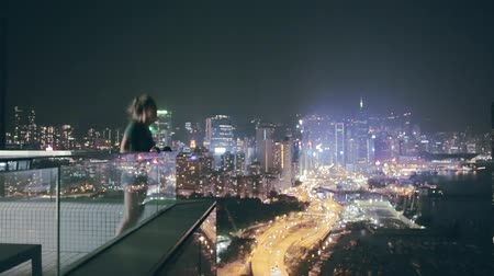 şaşırtıcı : Happy girl getting excited on the roof with amazing view over city at night. Hong Kong, China. Stok Video