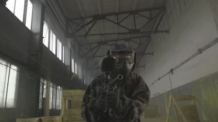 дичь : Paintball player in protective uniform and mask aiming gun before shooting. Player gets ready for the game. Violance and war concept.