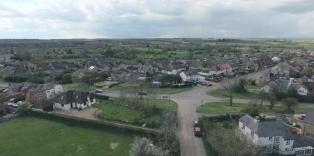 wielka brytania : Aerial view of UK middle class houses in small village or town in the countryside. Top view above houses surrounded by green lawns and farmland.