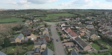 kasaba : Aerial view of UK middle class houses in small village or town in the countryside. Top view above houses surrounded by green lawns and farmland.