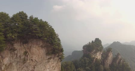 cliff : Aerial view of natural quartz sandstone pillar Avatar Hallelujah Mountain among green woods, mist,rocks in Tianzi Mountains, Zhangjiajie National Forest Park in Wulingyuan, Hunan Province, China.