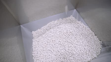 farmacologia : Pill Production. Closeup slow motion shot of many white pills falling out of pill manufacturing machi