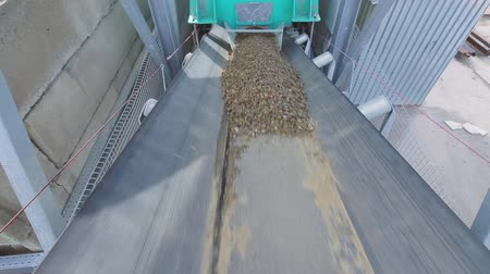 trackage : Sand, soil falling on conveyor belt on pile and moving along at construction site.Soil, gravel, sand, stones, separation and refinement process. Construction industry concept. Lockdown shot.