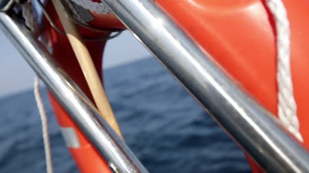 lifebelt : Red lifebuoy on the railing of the ship against background with sea and clear blue sky. Stock Footage