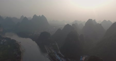 guangxi : Aerial shot of passenger boats,rafts in beautiful Li River surrounded by karst mountains at sunset or sunrise in Yangshuo,Guilin,China. Travel, picturesque famous destination and adventure concept.