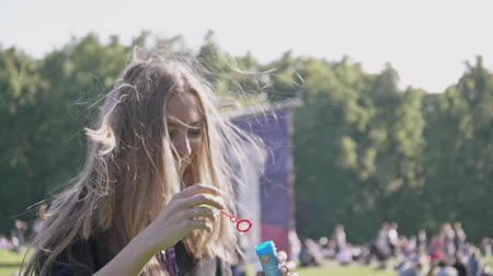 darbe : Beautiful young blonde girl blowing soap bubbles into the sky. Gorgeous young teen girl blowing bubbles. Outdoor summer portrait of attractive happy woman having fun in park or at nature. Stok Video