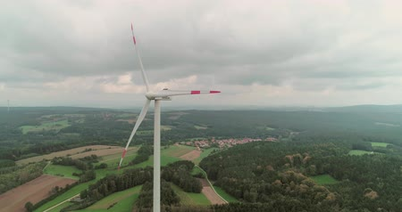 ветроэнергетики : Green power technology, production, clean and renewable energy solution concept. Aerial drone view of summer countryside with wind turbines and agricultural fields on a cloudy day,