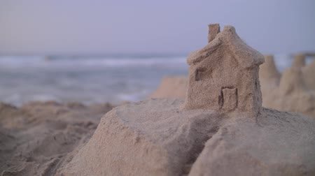 biztosítás : Handheld 4k shot of fortress or house from sand on the sea beach at sunset. Real estate, insurance and vacation concept. Stock mozgókép