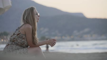 melankoli : Sad, depressed beautiful adult woman sitting on the beach and thinking. Young attractive blonde girl watching beautiful sunset alone. Loneliness, sadness concept. Stok Video