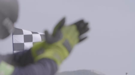 ралли : Man holding and waving Checkered race flag in slow motion at finish line on a raceway. Hands of unidentified person applauding.Victory, achievement, success and sport concept. Стоковые видеозаписи