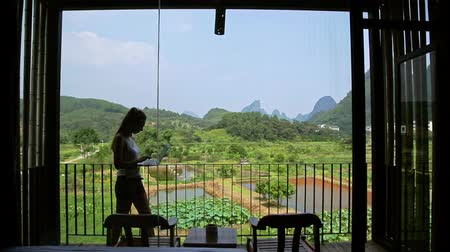 решение : Young woman surfing on internet outside the house on the terrace with a view over Guiling mountain landscape in Yangshuo County,China. Стоковые видеозаписи