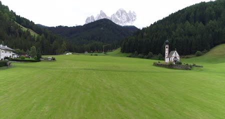 johann : Amazing aerial shot of Dolomiti mountain on a cloudy autumn day. Flying above beautiful green forest in Santa Maddalena in Val di Funes, Dolomites, Italy with view over Italian Alps. Stock Footage