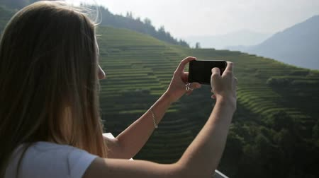 sapa people : Young attractive woman watching sunrise over Longji Rice Terraces from top of the mountain. Blonde beautiful girl takes panorama photos on phone.