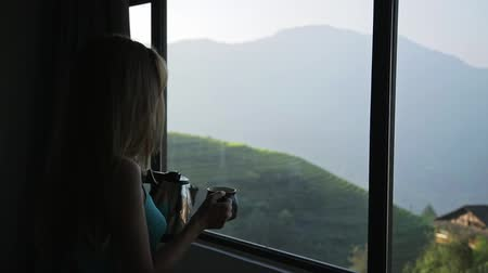 sapa people : Young beautiful woman enjoys her morning tea looking at the mountains and rice fields in famous Ping An Village, Longji,China. Freedom,Calmness and relax concept.Attractive girl holding cup of coffee Stock Footage