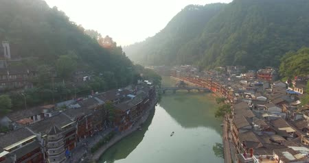 obec : Top view or aerial shot of famous ancient town in Fenghuang County, China. Flying over Green River, hills and houses of the village. Travel,destination and world heritage concept.