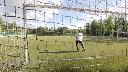 penas : Moscow, Russia - June 25, 2018 : Unidentified male goalkeeper standing behind the net of the gate in a public park Stock Footage