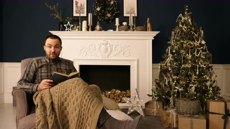 interessado : Portrait of a man reading book to the camera on Christmas evening.