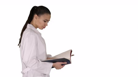 soma : Attractive medicine student or doctor with notebook walking and reading on white background.