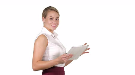 удивительный : Female office clerk walking with tablet and smiling broadly when talking to camera on white background. Стоковые видеозаписи
