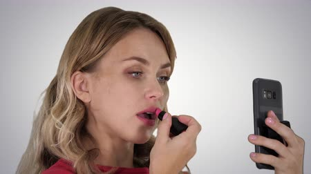 saç bantı : Beautiful stylish young woman applying red lipstick on lips and looking at phone screen on gradient background.