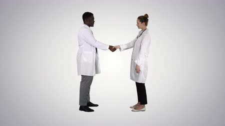 mustache : Two young doctor shaking hands on gradient background.